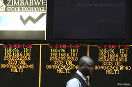A Zimbabwe Stock Exchange official walks past an electronic display screen showing an 11-percent drop at the close of trading, in Harare, Zimbabwe, August 5, 2013.