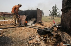 A man works at a makeshift oil refinery site in Aleppo's countryside, Apr. 2, 2013.