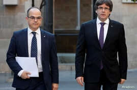 FILE - Catalan President Carles Puigdemont, right, walks with Catalan Government Presidency Councillor Jordi Turull as they arrive to a Cabinet meeting at the regional government headquarters in Barcelona, Spain, Oct. 17, 2017.