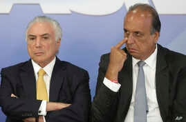 Brazil's President Michel Temer, left, sits next to the Governor of Rio de Janeiro Luiz Fernando Pezao, during the signing of a decree for the military intervention of Rio de Janeiro's local police, in Brasilia, Brazil, Feb. 16, 2018.