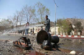 Afghan firefighters clean up the site of a deadly suicide bombing near Kabul University, in Kabul, March 21, 2018.