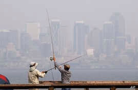 A pair of anglers uncross their lines while fishing in Elliott Bay as a smoky haze obscures downtown Seattle in the background, Aug. 14, 2018. Public-health officials Wednesday warned of unhealthy air across many parts of the Pacific Northwest as wil