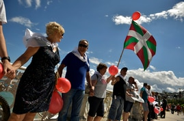 A man holds up a Basque flag, or Ikurrina, as people gather along La Concha beach to make a human chain calling for the independence of the Basque Country with the slogan ''Our Right to Decide'' or in Basque language, ''Gure Esku Dago,'' in the Basqu