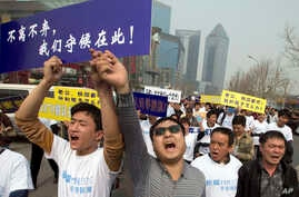 Chinese relatives of passengers onboard the missing Malaysia Airlines plane, flight MH370, shout in protest as they march towards the Malaysia embassy in Beijing, China, March 25, 2014.