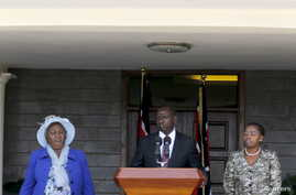 Kenya's Deputy President William Ruto (C) flanked by his wife Rachel Ruto (R) and mother Sarah Cherono (L) addresses a news conference on the ruling by the International Criminal Court (ICC) on the case against him and broadcaster Joshua Sang in Nair