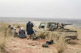 FILE - Militants of the Movement for the Salvation of Azawad stand on a dune in the deserted area of the Meneka region in Mali during an anti-jihadist patrol, Feb. 4, 2018. Suspected jihadists briefly seized a military camp in the central Mopti regio