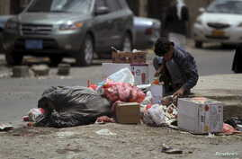 A boy searches for food amongst litter in Sanaa, April 8, 2015.