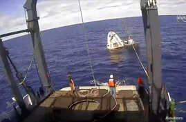 An unmanned capsule of the SpaceX Crew Dragon spacecraft is seen shortly after splashing down into the Atlantic Ocean as SpaceX recovery teams works on it, in this still image from video from NASA Commercial Crew, in the Atlantic, about 200 miles off