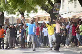 In this photo taken Monday, Oct. 26th, 2015 and made available Wednesday, Oct. 28th, 2015, youths supporting the opposition party dance and chant, predicting a win for their candidate, outside the Electoral Commission office in Stone Town, Zanzibar,