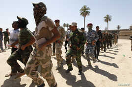 Shi'ite volunteers, who have joined the Iraqi army to fight against militants of the Islamic State, formerly known as the Islamic State in Iraq and the Levant (ISIL), march during training in Baghdad, July 9, 2014.