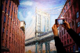 "A woman takes a picture of a painting by Bob Dylan called ""Manhattan Bridge, Downtown New York"" on display at the exhibition called Bob Dylan The Beaten Path, at the Halcyon Gallery in London, Tuesday, November. 1, 2016. The exhibition opens on Novem"