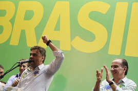 Brazilian Social Democratic Party presidential candidate Aecio Neves talks to supporters next to his vice-presidential running mate Aloysio Nunes (R) during their campaign rally in Sao Paulo October 15, 2014.