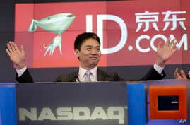 Qiangdong Liu, CEO of JD.com, raises his armsprior to the opening of the Nasdaq market, Thursday, May 22, 2014 in New York.