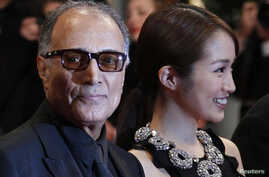 """FILE - Director Abbas Kiarostami (L) and cast member Rin Takanashi arrive on the red carpet for the screening of the film """"Like Someone in Love"""", in competition at the 65th Cannes Film Festival, May 21, 2012."""