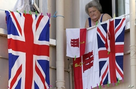 FILE - A woman resident of Gibraltar looks out of a window behind flags of England and Gibraltar, Aug. 4, 2004. For British-ruled Gibraltarians, London's membership in the EU prodives a safety net they would lose if Britain were to exit the EU.