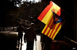 People walk past a Spanish and an estelada, or independence flag, hanging up for sale in a shop in Barcelona, Spain, Oct. 11, 2017.