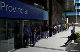 People line up to withdraw cash from an automated teller machine outside a Banco Provincial branch in Caracas, Venezuela, Dec. 12, 2016.