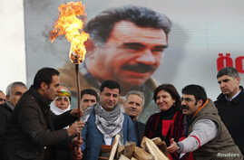 Selahattin Demirtas (front C), co-chairman of the pro-Kurdish Peace and Democracy Party (BDP), lights a traditional Newroz fire during a rally to celebrate the spring festival of Newroz - with a picture of imprisoned PKK leader Abdullah Ocalan seen i
