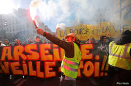 """A protester wearing a yellow vest holds a flare as he takes part in a demonstration of the """"yellow vests"""" movement in Marseille, France, January 26, 2019."""