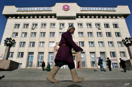 FILE - A  Mongolian man walks along  Ulan Bator's vast central square near the parliament building in Mongolia.