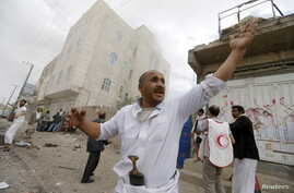 People react at the site of a Saudi-led coalition airstrike in Sana'a, Yemen, April 8, 2015.