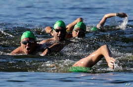 In this July 6, 2017 photo, a group of swimmers - called the River Huggers - head upstream in the Willamette River in downtown Portland, Oregon.