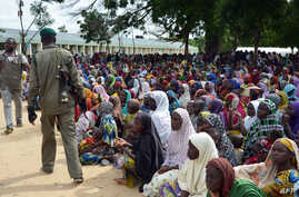 A policeman walks past dozens of people, who have been displaced from their communities after attacks by the Islamist group Boko Haram, at a camp for internally displaced people in Maiduguri, August 3, 2015.