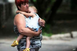 An unidentified refugee woman, carries a young girl, near a dormitory, after being displaced due to shelling, in the city of Donetsk, eastern Ukraine, July 13, 2014.