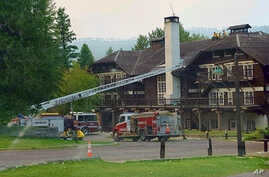 This Sept. 3, 2017 photo provided by the National Park Service shows fire truck positioned outside Lake McDonald Lodge in Glacier National Park, Montana, as firefighters prepare for a blaze that is threatening the century-old Swiss chalet-style hotel