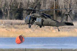 A National Guard helicopter picks up water from a farm pond near Hutchinson, Kansus, March 7, 2017.