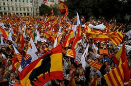 """People wave flags of Catalonia and Spain as they celebrate a holiday known as """"Dia de la Hispanidad"""" or Spain's National Day in Barcelona, Spain, Oct. 12, 2017."""