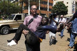 A journalist rescues a woman injured in a shootout between armed men and the police at the Westgate shopping mall in Nairobi September 21, 2013. (Reuters/Thomas Mukoya)