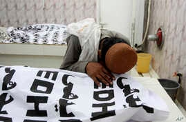 A Pakistani mourns over a dead body of his family member who is killed in a bomb attack, at a mortuary in Quetta, Pakistan, July 13, 2018.