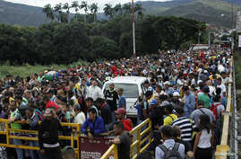 FILE - People queue to try to cross the Venezuela-Colombia border through Simon Bolivar international bridge in San Antonio del Tachira, Venezuela, Aug. 3, 2018.