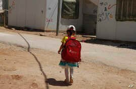 A girl walks to school in the Zaatari Refugee Camp for Syrian refugees, in northern Jordan, Aug. 6, 2017.