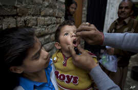 FILE - A Pakistani health worker gives a polio vaccine to a child in Islamabad, Dec. 8, 2014.