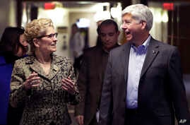 FILE - Michigan Gov. Rick Snyder and Ontario Premier Kathleen Wynne walk to a news conference, March 13, 2017, in Detroit. Snyder and Wynne stressed that they want their voices heard as President Donald Trump demands a negotiation of trade policies b