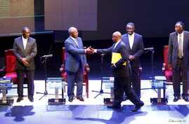 Uganda President Yoweri Museveni (with file) shakes hands with Amama Mbabazi, former prime minister and The Democratic Alliance (TDA) presidential candidate, during a presidential debate in Kampala, Feb. 13, 2016.