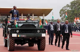 Ivory Coast's President Alassane Ouattara salutes while standing in a military vehicle during a parade to commemorate the country's 56th Independence Day outside the presidential palace in Abidjan, Aug. 7, 2016.