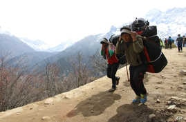 FILE - Nepalese porters carry heavy loads for climbers on their way to Everest Base Camp at Kyangjuma, Nepal in this April 7, 2015 photo..