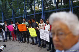 Migrants from Central America hold candles during a protest demanding a reform in U.S. immigration laws which regulate the illegal exodus of children into the U.S., and to provide protection for them, outside the U.S. embassy in Mexico City, August 9