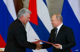 Russian President Vladimir Putin, right, and Cuban President Miguel Diaz-Canel, exchange documents after their talks in the Kremlin, in Moscow, Russia, Nov. 2, 2018.