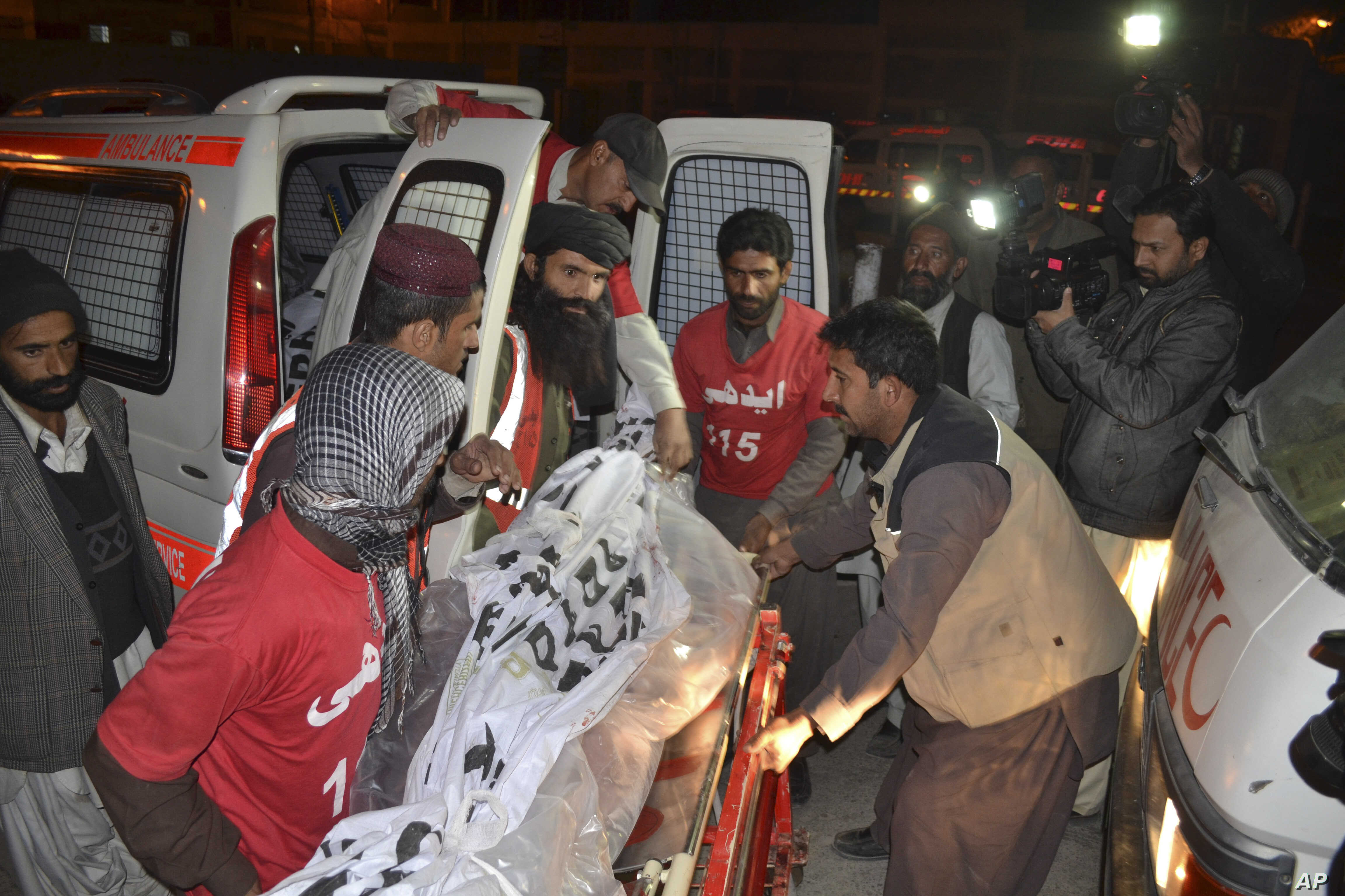 Pakistani volunteers carry the body of a militant killed during a crackdown by security forces, in Quetta, Dec. 19, 2014.
