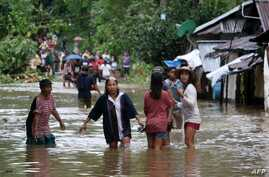 Villagers wade through a flooded street in Brgy Calingatngan, in Borongan, easterm Samar, central Philippines, Dec. 16, 2017.