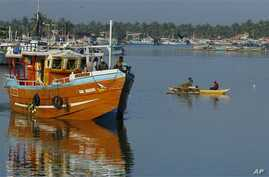 Lankan fishermen stand on a fishing vessel as it leaves a fishery harbor in Negombo, Negombo, outskirts of Colombo, Sri Lanka, Wednesday, Oct.15, 2014. In its fight against illegal fishing activities worldwide, the European Commissioner for Maritime