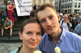 FILE - Ukrainian activist Lyudmyla Kozlovska (L), and her husband Bartosz Kramek are seen during an anti-government protest in Warsaw, Poland, Aug. 10, 2017.