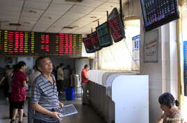 An investor looks at electronic boards showing stock information at a brokerage house in Shanghai, China, Sept. 1, 2015.