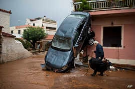 A man walks past a car moved by the force of flood water and a damaged house in the town of Mandra western Athens, Nov. 16, 2017. Greece's fire department says rescue crews are searching for six people reported missing in the western Athens area foll
