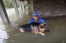 Joe Garcia carries his dog, Heidi, from his flooded home as he is rescued from rising floodwaters from Tropical Storm Harvey, Aug. 28, 2017, in Spring, Texas.