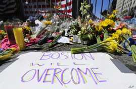 FILE - Flowers and signs adorn a barrier, two days after two explosions killed three and injured hundreds, at Boylston Street near the of finish line of the Boston Marathon at a makeshift memorial for victims and survivors, April 17, 2013.